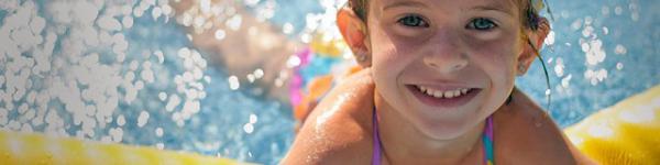 Nena somrient a una piscina