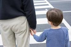 Niño cruzando por paso peatonal con su padre