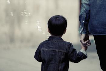 Adult donant la mà a un nen