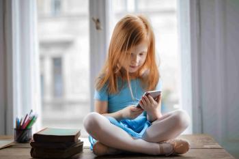 Nena amb un telèfon intel·ligent a casa