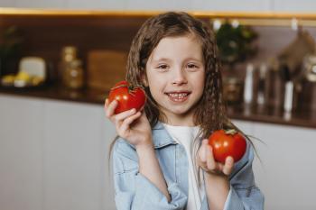 Niña sonriente con tomates