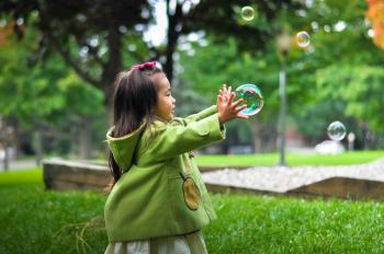 Nena jugant amb bombolles de sabó