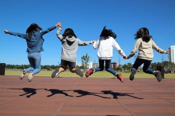 Nenes de la mà saltant al pati