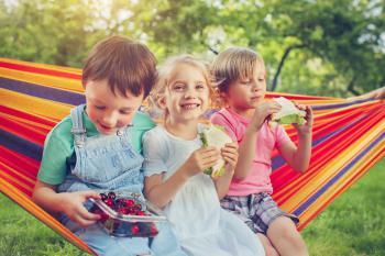 Niños merendando en una hamaca al aire libre