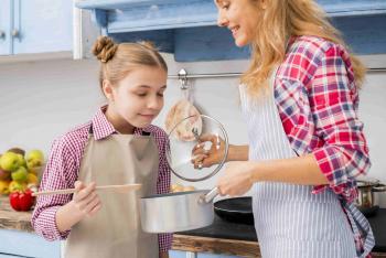 Nena fent olor el menjar en la cuina