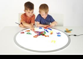 nens jugant amb la taula de llum TickIT