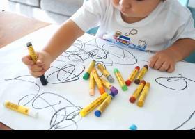 Nen dibuixant amb ceres de colors