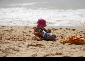 Bebè jugant a la platja