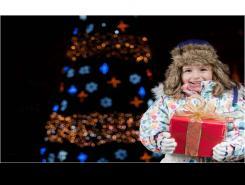 Nena amb un regal davant un arbre de Nadal