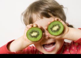 Niña tapándose los ojos con dos trozos de kiwi