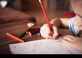 Nena escrivint en paper