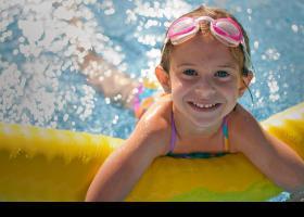 Niña sonriendo en una piscina