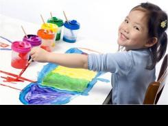 Nena pintant amb pintures