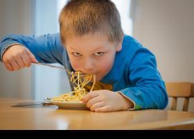 Niños comiendo un plato de pasta