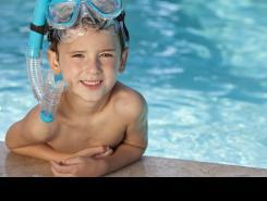 Nen a la piscina amb ulleres i tub de bussejar