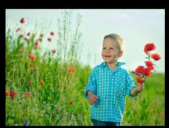 Nen amb flors en un camp