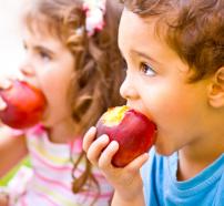 Niños comiendo manzanas