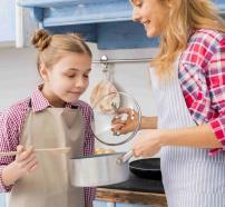 Niña oliendo la comida en la cocina