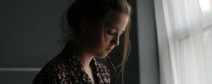 Chica triste mirando por la ventana