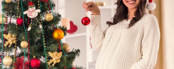 Mujer embarazada frente a un árbol de Navidad